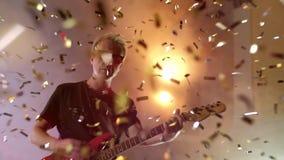 Ο κιθαρίστας αποδίδει στη σκηνή Σκηνικό φως, καπνός Άνωθεν χρυσό κομφετί πτώσης φιλμ μικρού μήκους