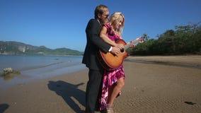 Ο κιθαρίστας βοηθά την ξανθή κιθάρα παιχνιδιού κοριτσιών απόθεμα βίντεο