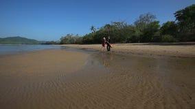 Ο κιθαρίστας και το κορίτσι στα υψηλά παπούτσια τακουνιών περπατούν στη θάλασσα κάτω από τη χαμηλή παλίρροια απόθεμα βίντεο