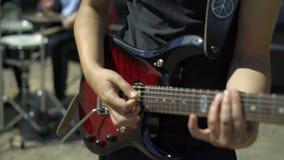 Ο κιθαρίστας με μια κόκκινη ηλεκτρική κιθάρα παίζει τη φοβιτσιάρη μουσική με τον τυμπανιστή στην οδό Τα αρσενικά χέρια παίρνουν μ φιλμ μικρού μήκους