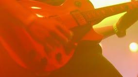 Ο κιθαρίστας μολύβδου αποδίδει στο στάδιο με μια ορχήστρα ροκ φιλμ μικρού μήκους