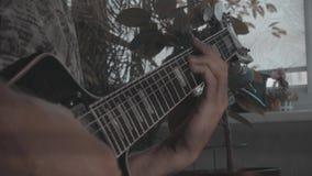 Ο κιθαρίστας μουσικών παίζει riffs σε αυτήν την μαύρη ηλεκτρική κιθάρα απόθεμα βίντεο