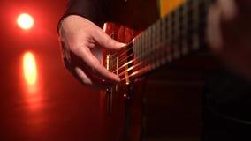 Ο κιθαρίστας παίζει μια μελωδία κλείστε επάνω Φως από πίσω απόθεμα βίντεο