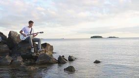 Ο κιθαρίστας παίζει τις ηλεκτρικές χορδές κιθάρων στην ακτή FHD απόθεμα βίντεο