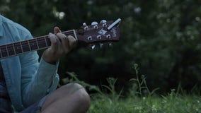 Ο κιθαρίστας στερεώνει τη χορδή του με τα δάχτυλά του απόθεμα βίντεο