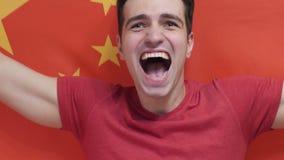 Ο κινεζικός νεαρός άνδρας γιορτάζει το κράτημα της σημαίας της Κίνας σε σε αργή κίνηση απόθεμα βίντεο