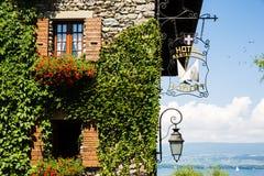 Ο κισσός κάλυψε τον πέτρινο τοίχο με τα κόκκινες λουλούδια, τις βάρκες και τη λίμνη σε έναν ήλιο στοκ εικόνες
