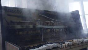 Ο κλασικός που ξεχνιούνται και το σπασμένο ξύλινο πιάνο καπνίζουν μετά από να τεθούν από την πυρκαγιά απόθεμα βίντεο