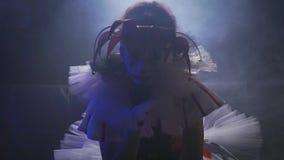 Ο κλόουν κοριτσιών σε ένα φόρεμα, ένα καπέλο και makeup κάθεται στο σκοτει απόθεμα βίντεο
