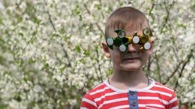 Ο κλώστης στα γυαλιά περιστρέφει Διασκέδαση στην οδό Ένα παιδί στο υπόβαθρο των ανθίζοντας άσπρων λουλουδιών του κερασιού απόθεμα βίντεο