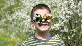 Ο κλώστης στα γυαλιά περιστρέφει Διασκέδαση στην οδό Ένα παιδί στο υπόβαθρο των ανθίζοντας άσπρων λουλουδιών του κερασιού φιλμ μικρού μήκους