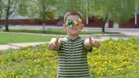 Ο κλώστης στα γυαλιά περιστρέφει Διασκέδαση στην οδό Αγόρι σε ένα υπόβαθρο των κίτρινων λουλουδιών, πικραλίδες απόθεμα βίντεο