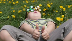Ο κλώστης στα γυαλιά περιστρέφει Διασκέδαση στην οδό Αγόρι σε ένα υπόβαθρο των κίτρινων λουλουδιών, πικραλίδες φιλμ μικρού μήκους