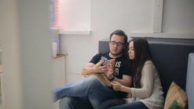 Ο κοβάλτιο-εργαζόμενοι άνδρας και η γυναίκα εργάζονται με το τηλέφωνο κυττάρων απόθεμα βίντεο