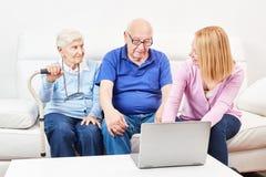 Ο κοινωνικός λειτουργός παρουσιάζει φορητό προσωπικό υπολογιστή ατόμων τρίτης ηλικίας στοκ εικόνες με δικαίωμα ελεύθερης χρήσης