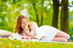 Ο κοκκινομάλλης σπουδαστής τρώει τα βιβλία μήλων και ανάγνωσης Στοκ φωτογραφίες με δικαίωμα ελεύθερης χρήσης