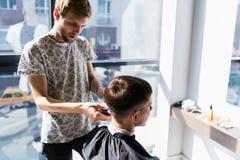 Ο κομμωτής ισοπεδώνει ένα κούρεμα με τη βοήθεια ενός ηλεκτρικού ξυραφιού και μιας χτένας σε ένα barbershop στοκ εικόνες με δικαίωμα ελεύθερης χρήσης