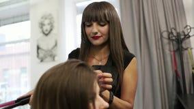 Ο κομμωτής κάνει ένα hairstyle για μια γυναίκα Κινηματογράφηση σε πρώτο πλάνο κουρέματος Ψαλίδι και χτένα στην όμορφη τρίχα στιλί φιλμ μικρού μήκους