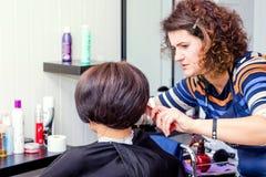 Ο κομμωτής κάνει τη γυναίκα το μοντέρνο hairstyle Επαγγελματικό hairdr στοκ φωτογραφία