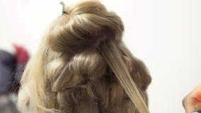 Ο κομμωτής κάνει hairstyle με το κατσάρωμα του σιδήρου στη γυναίκα απόθεμα βίντεο