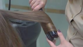 Ο κομμωτής κάνει hairstyle την κινηματογράφηση σε πρώτο πλάνο στα ξανθά μαλλιά της όμορφης γυναίκας απόθεμα βίντεο