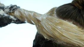 Ο κομμωτής κάνει hairstyle, χρωστική ουσία για έναν έφηβο σε ένα σαλόνι ομορφιάς Τρίχα που καλύπτεται στη χρωστική ουσία κίνηση α φιλμ μικρού μήκους