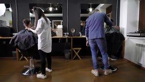 Ο κομμωτής και ο συνάδελφός του έκοψαν την τρίχα γιατί δύο άτομα που ήρθαν στο σαλόνι ομορφιάς για τα άτομα, πελάτες κάθονται στι απόθεμα βίντεο