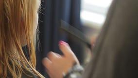 Ο κομμωτής κουρεύει μια γυναίκα με τα μακριά ξανθά μαλλιά Κινηματογράφηση σε πρώτο πλάνο κουρέματος απόθεμα βίντεο