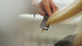 Ο κομμωτής κουρεύει μια γυναίκα με τα μακριά ξανθά μαλλιά Κινηματογράφηση σε πρώτο πλάνο κουρέματος φιλμ μικρού μήκους