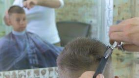 Ο κομμωτής κόβει την τρίχα αγοριών ` s με το ψαλίδι στο barbershop απόθεμα βίντεο