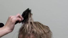 Ο κομμωτής ξεραίνει την ξανθή τρίχα με έναν στεγνωτήρα τρίχας και μια βούρτσα τρίχας απόθεμα βίντεο