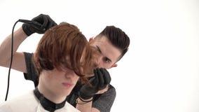 Ο κομμωτής στιλίστων κάνει ένα μοντέρνο Hairstyle το νέο τύπο με την κόκκινη τρίχα απόθεμα βίντεο