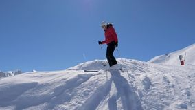 Ο κομψός σκιέρ που κάνει σκι κάτω στην άκρη της κλίσης σκι και θαυμάζει το πανόραμα απόθεμα βίντεο