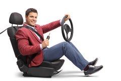 Ο κομψός τύπος κάθισε σε ένα κάθισμα αυτοκινήτων που κρατά ένα τιμόνι και ένα α Στοκ Φωτογραφίες