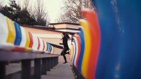 Ο κορίτσι-αθλητής τρέχει γρήγορα κοντά στα καθίσματα θεατών στο στάδιο απόθεμα βίντεο