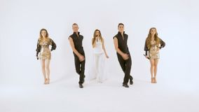 Ο κορίτσι-τραγουδιστής σε ένα άσπρο φόρεμα δύο νεαροί άνδρες στα μαύρα κοστούμια χορεύει Δύο όμορφα κορίτσια με μακρυμάλλη σε λαμ απόθεμα βίντεο