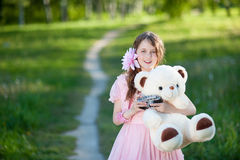 Ο κορίτσι-φωτογράφος σε ένα ρόδινο φόρεμα που αγκαλιάζει μια teddy αρκούδα Στοκ Εικόνα