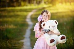 Ο κορίτσι-φωτογράφος σε ένα ρόδινο φόρεμα που αγκαλιάζει μια teddy αρκούδα Στοκ εικόνα με δικαίωμα ελεύθερης χρήσης