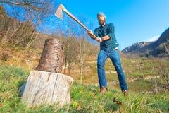 Ο κορμός του ξύλου είναι περίπου να κοπεί με ένα γενειοφόρο άτομο τσεκουριών Στοκ εικόνα με δικαίωμα ελεύθερης χρήσης