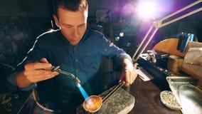 Ο κοσμηματοπώλης λειώνει το μέταλλο εργαζόμενος σε ένα εργαστήριο Jeweler, χρυσοχόος σε ένα επαγγελματικό εργαστήριο κοσμήματος απόθεμα βίντεο