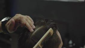 Ο κουρέας κόβει την τρίχα του πελάτη με το ψαλίδι o Το ελκυστικό αρσενικό παίρνει ένα σύγχρονο κούρεμα στο κατάστημα κουρέων απόθεμα βίντεο