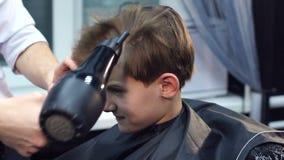 Ο κουρέας ξεραίνει την τρίχα στο αγόρι με ένα hairdryer απόθεμα βίντεο