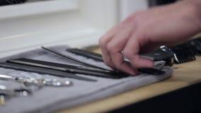 Ο κουρέας παίρνει το ψαλίδι και τη χτένα από έναν πλήρη πίνακα εργαλείων απόθεμα βίντεο
