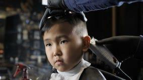 Ο κουρέας στα μαύρα γάντια ξυρίζει ήπια την τρίχα πίσω από τα αυτιά ενός ασιατικού παιδιού 60 fps φιλμ μικρού μήκους