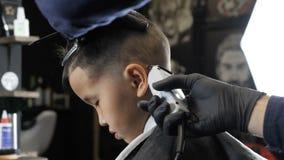 Ο κουρέας στα μαύρα γάντια ξυρίζει ήπια την τρίχα πίσω από τα αυτιά ενός ασιατικού παιδιού, πλάγια όψη 60 fps απόθεμα βίντεο