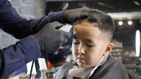 Ο κουρέας στα μαύρα γάντια ξυρίζει ήπια το λυπημένο ασιατικό παιδί 60 κτυπημάτων fps φιλμ μικρού μήκους