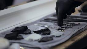 Ο κουρέας στα μαύρα γάντια παίρνει το ψαλίδι και τη χτένα από έναν πλήρη πίνακα εργαλείων φιλμ μικρού μήκους
