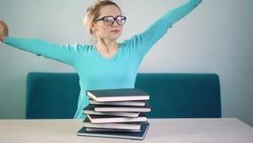 Ο κουρασμένος, 0, εξαντλημένος σπουδαστής χαμήλωσε το κεφάλι της σε έναν σωρό των βιβλίων Πρέπει να διαβάσετε πολλά βιβλία πολλή  φιλμ μικρού μήκους