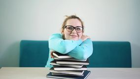 Ο κουρασμένος, 0, εξαντλημένος σπουδαστής χαμήλωσε το κεφάλι της σε έναν σωρό των βιβλίων Πρέπει να διαβάσετε πολλά βιβλία πολλή  απόθεμα βίντεο