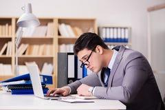 Ο κουρασμένος επιχειρηματίας που εργάζεται στο γραφείο Στοκ εικόνα με δικαίωμα ελεύθερης χρήσης